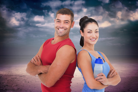 Fit man and woman smiling at camera together against dark cloudy sky photo
