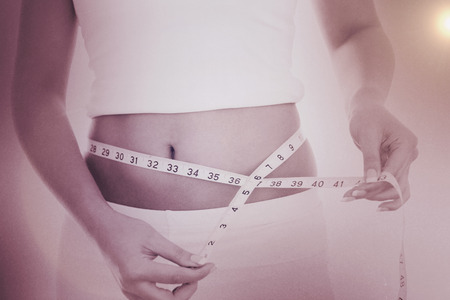 woman measuring waist: Midsection of woman measuring waist against grey Stock Photo