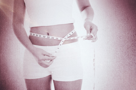 body concern: Midsection of woman measuring waist against weathered surface Stock Photo