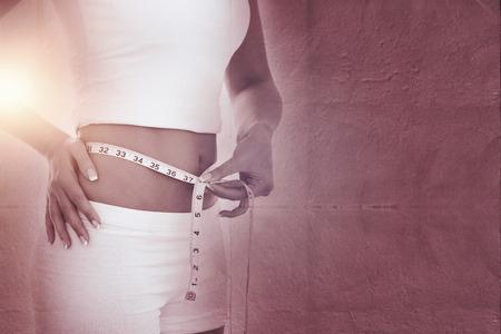 woman measuring waist: Midsection of woman measuring waist against grey concrete tile