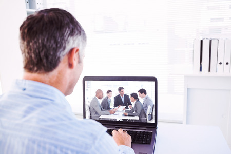 grey hair: Man with grey hair using his laptop against business people disscussing a budget plan Stock Photo