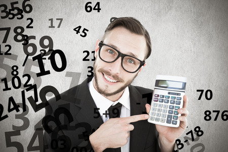 cheesy grin: Geeky businessman pointing to calculator  against white background Stock Photo