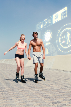 Fit couple rollerblading on the promenade  against fitness interface