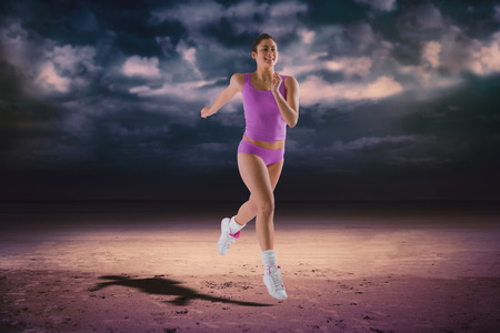 Fit brunette running and jumping against dark cloudy sky photo