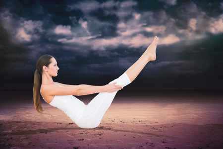 Toned woman doing the boat pose in fitness studio against dark cloudy sky photo