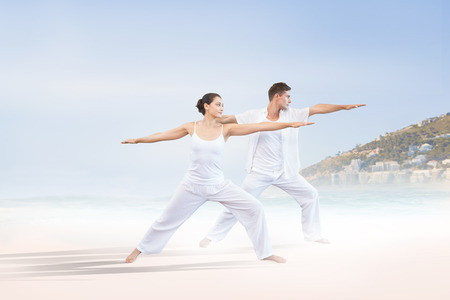 guy on beach: Peaceful couple in white doing yoga together in warrior position against beautiful beach and blue sky