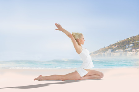 backwards: Toned young woman stretching hands backwards against beautiful beach and blue sky Stock Photo