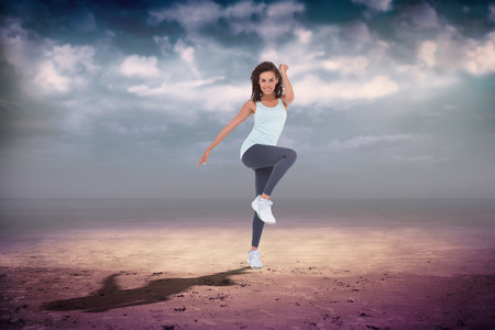 Fit woman doing aerobic exercise against dark cloudy sky photo
