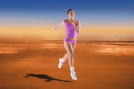 hazy: Fit brunette running and jumping against hazy blue sky