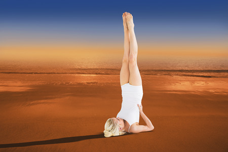 hazy: Fit young woman doing the shoulder stand pose against hazy blue sky Stock Photo