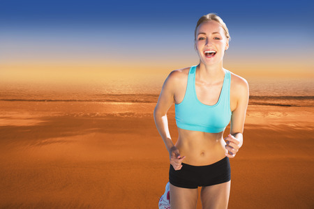 hazy: Fit woman smiling and jogging  against hazy blue sky