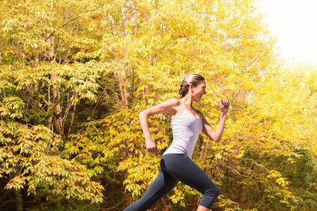 Pretty fit blonde jogging  against peaceful autumn scene in forest