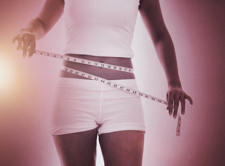 body concern: Midsection of woman measuring waist against grey Stock Photo