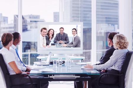 Gruppe von Geschäftsleuten Blick auf einen Schirm gegen Porträt eines positiven Teams, die an einem Tisch