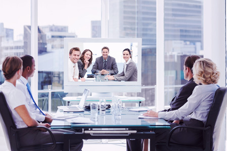 Group of business people looking at a screen against portrait of a positive team sitting at a table
