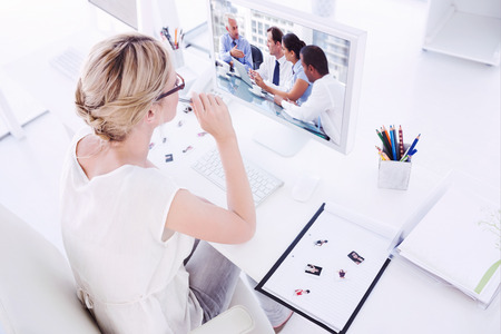 Female photo editor working on computer against group of business people brainstorming together photo