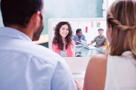 computer monitor: Colleagues looking at computer against smiling woman with creative team working behind Stock Photo