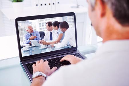 usando computadora: El hombre con el pelo gris escribiendo en la computadora portátil contra el grupo de personas de negocios de intercambio de ideas entre sí