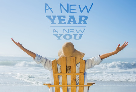 Woman relaxing in deck chair by the sea against new year new you Stock Photo