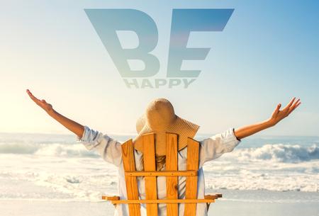 Die Frau, die im Klappstuhl durch das Meer gegen sich entspannt, ist glücklich