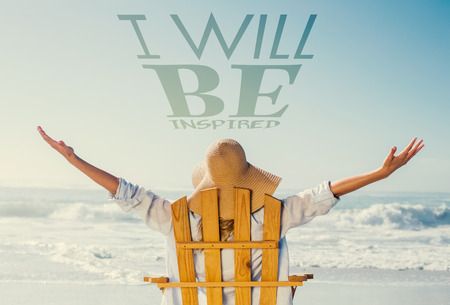 Woman relaxing in deck chair by the sea against i will be inspired Stock Photo