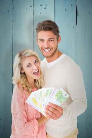 Attractive couple flashing their cash against painted blue wooden planks