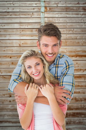 pale wood: Attractive young couple smiling at camera against wooden background in pale wood