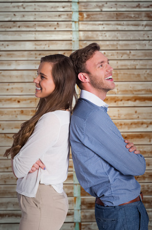 fade away: Happy young couple standing back to back against wooden background in pale wood