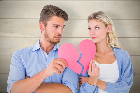 Couple holding two halves of broken heart against bleached wooden planks background