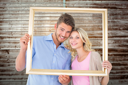 Attractive young couple holding picture frame against wooden planks photo