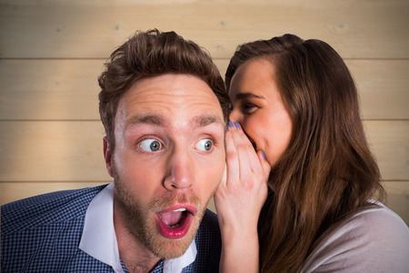Woman whispering secret into friends ear against bleached wooden planks background Standard-Bild