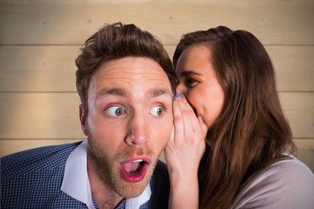 secrets: Woman whispering secret into friends ear against bleached wooden planks background Stock Photo