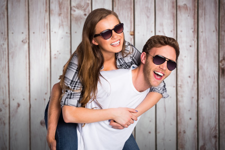 man carrying woman: Smiling young man carrying woman against wooden planks