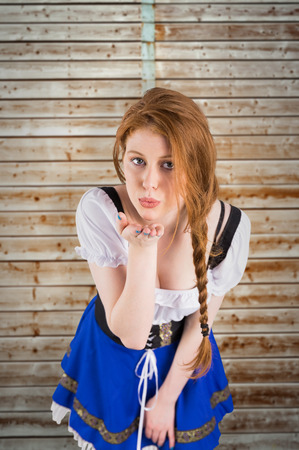 pale wood: Oktoberfest girl blowing a kiss against wooden background in pale wood