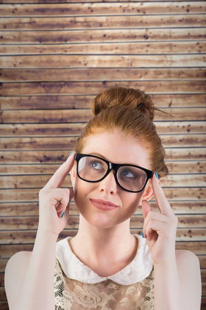 inquiring: Hipster redhead looking up thinking against wooden planks