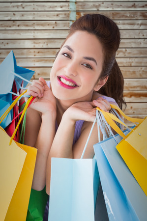 pale wood: Portrait of a happy brunette holding shopping bags against wooden background in pale wood