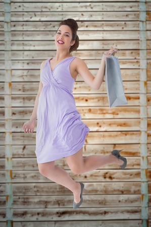 pale wood: Happy brunette jumping with shopping bag against wooden background in pale wood