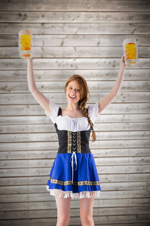 jugs: Oktoberfest girl holding jugs of beer against wooden planks background