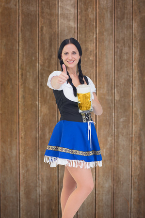 tankard: Pretty oktoberfest girl holding beer tankard against wooden planks background