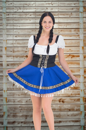 pale wood: Pretty oktoberfest girl posing and smiling against wooden background in pale wood Stock Photo