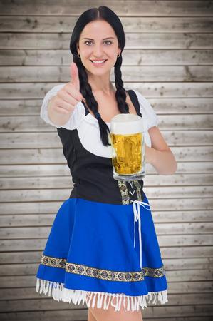 tankard: Pretty oktoberfest girl holding beer tankard against wooden planks background