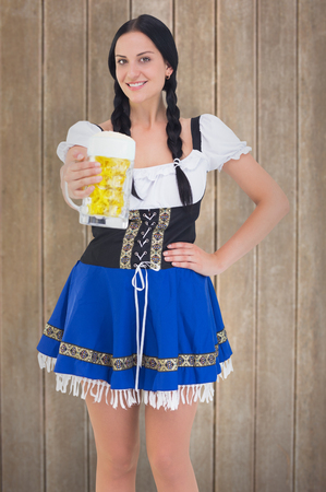 tankard: Pretty oktoberfest girl holding beer tankard against wooden surface with planks Stock Photo
