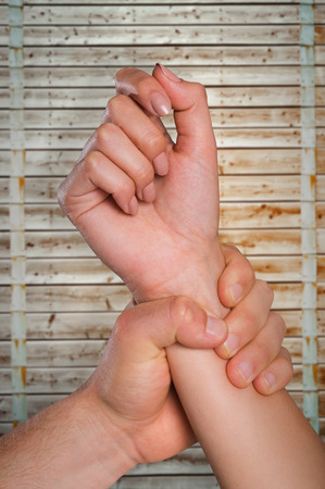 cowering: Male hand grabbing female wrist against wooden background in pale wood