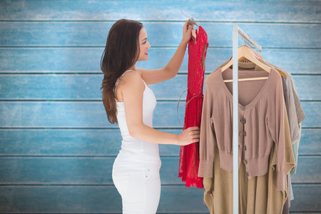 choosing clothes: Woman choosing clothes against wooden planks