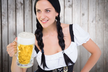 tankard: Pretty oktoberfest girl holding beer tankard against wooden planks