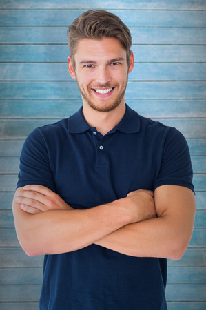 arms folded: Handsome young man smiling with arms crossed against wooden planks