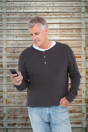 pale wood: Casual man sending a text against wooden background in pale wood Stock Photo