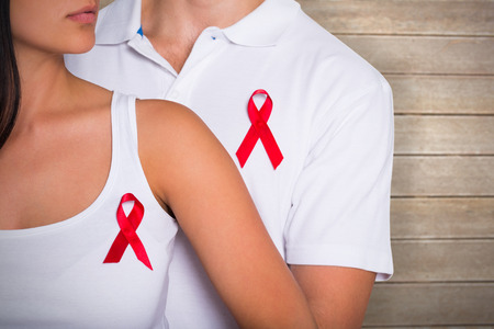 Couple supporting aids awareness together against wooden surface with planks photo