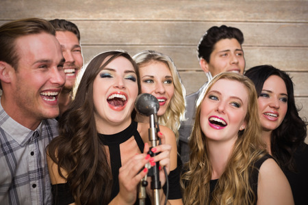 karaoke: Friends singing karaoke against wooden surface with planks Stock Photo