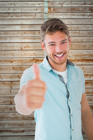 pale wood: Handsome young man showing thumbs up to camera against wooden background in pale wood